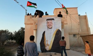 Supporters of Myasar Sardeyeh suspend a picture of Jordan's King Abdullah in front her electoral HQ