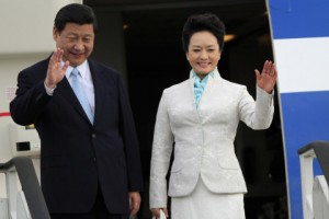 Chinese President Xi Jinping and First Lady Peng Liyuan wave from their plane upon their arrival at Julius Nyerere International Airport in Dar es Salaam