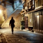 13933871-woman-walking-alone-along-a-cobblestone-road-at-night-in-kyoto-japan