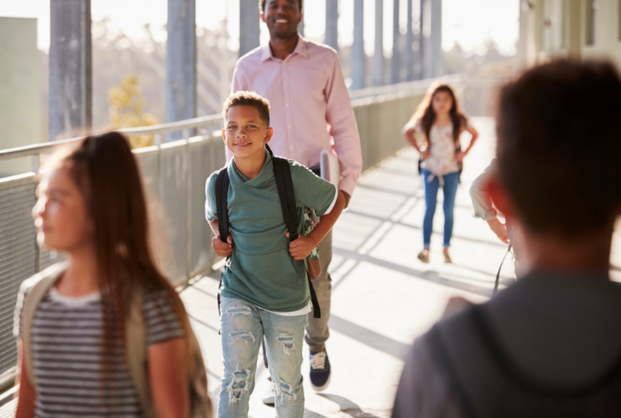 kids walking in school campus with adult
