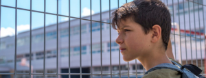 Kid in front of a school gate